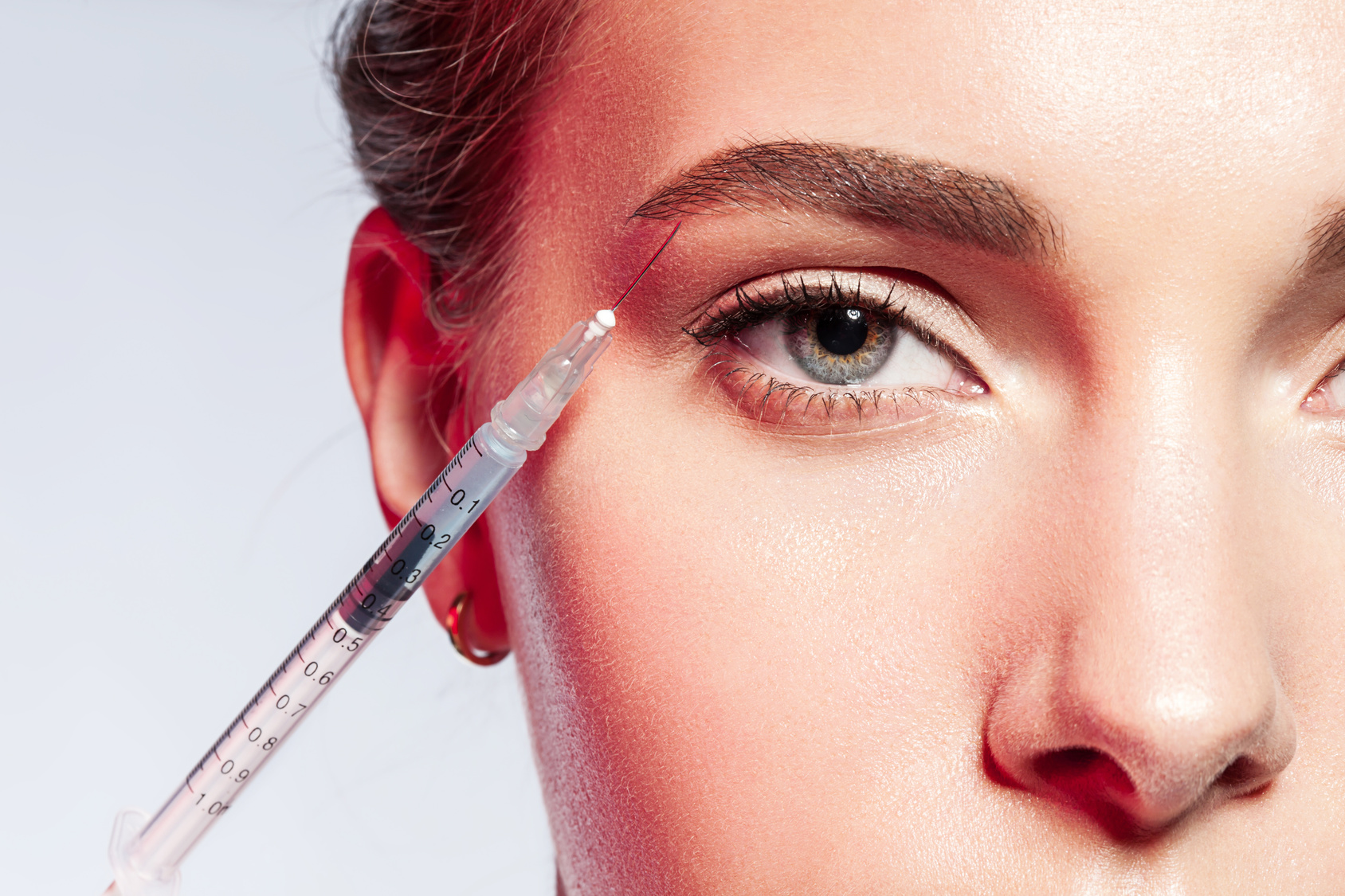 close-up of a woman doing an injection under the eyebrow